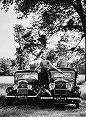 Image Exclusive * Femme posant debout sur deux Peugeot 201 et une Peugeot 301 dans un pré en 1932.