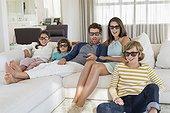 Famille qui regarde la télévision à la maison avec des lunettes 3D