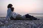 Young couple lying on beach, woman pregnant, sunset