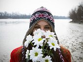 Young woman outdoors holding flowers up to face, portrait