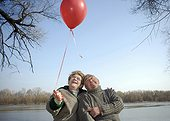Senior couple by river holding red balloon, smiling