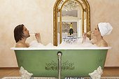 young couple sitting in bath drinking champagne, side view