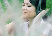 Woman listening to headphones, vegetation in foreground