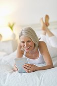 Senior woman lying on bed and using digital tablet