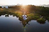 Austria, Salzburg County, Young woman sitting near mountain lake and doing meditation