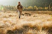 Austria, Salzburg, Young woman running in autumn