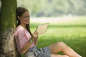 Germany, North Rhine Westphalia, Cologne, Young student sitting in park with digital tablet, smiling