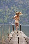 Austria, Teenage girl running on jetty