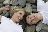 Portrait of young couple lying on rocky beach