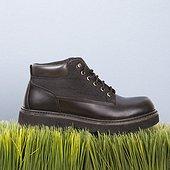 Studio shot of black leather shoe resting on grass.
