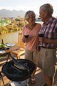 Happy senior couple having wine in the backyard