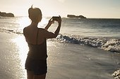 Female volleyball player taking photo with mobile phone on the beach