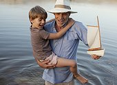 Smiling grandfather and grandson with toy sailboat wading in lake