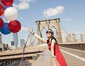Woman with bunch of balloons on urban bridge