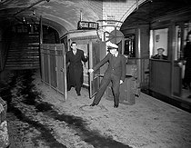 Roger-Viollet | 154990 | Subway employee holding back the automatic gate so that a traveller could board a metro. Paris, on January 1947. There is a notice on the wall behind the employee dating back to the Liberation. | © Roger-Viollet / Roger-Viollet