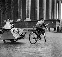 Roger-Viollet | 166549 | World War II. Wedding on a cycle taxi, at the place de la Madeleine. Paris, December 1941. | © LAPI / Roger-Viollet