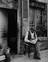 Roger-Viollet | 168767 | Man reading the newspaper sitting in front of his house. Semur-en-Auxois (Côte-d'Or), 1954. Photograph by Janine Niepce (1921-2007). | © Janine Niepce / Roger-Viollet