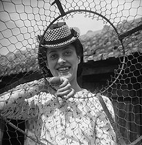 Roger-Viollet   179676   Young woman behind the wire netting of a hen coop. France, July 1941.   © Pierre Jahan / Roger-Viollet