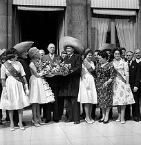 Roger-Viollet | 192892 | Charles de Gaulle (1890-1970), President of the French Republic, and his wife Yvonne (1900-1979), receiving lily of the valley from the market porters and the queens of the Halles covered market, on May 1st, 1960. | © Roger-Viollet / Roger-Viollet
