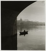 Roger-Viollet | 196095 | Fisherman on his rowing boat, under the Pont-Neuf, Paris (Ist and VIth arrondissement). 1936. Photograph by Roger Schall (1904-1995). Paris, musée Carnavalet. | © Roger Schall / Musée Carnavalet / Roger-Viollet