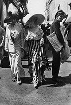 Roger-Viollet | 209560 | France - Elegant women and newspaper seller | © Maurice-Louis Branger / Roger-Viollet
