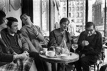 Roger-Viollet | 210113 | French director Claude Chabrol and the actors of his first two movies at the café  Les Deux-Magot : Bernadette Lafont, Gérard Blain, Jean-Claude Brialy and Juliet Mayniel. Paris, April 1959. | © Bernard Lipnitzki / Roger-Viollet