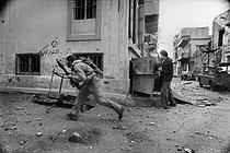 Roger-Viollet | 227207 | Lebanese civil war. Christian militiamen, members of the Kataeb party, running after Palestinian from the Quarantine district. Beirut (Lebanon), January 1976. | © Françoise Demulder / Roger-Viollet