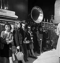 Roger-Viollet | 238211 | World War II. Liberation of Paris. Crowd listening to General de Gaulle's speech, broadcasted on the radio  Le Matériel Téléphonique  from the Chaillot palace. Paris (IXth arrondissement), Opéra Garnier, September 12, 1944. Photograph by Jean Roubier (1896-1981). | © Fonds Jean Roubier / Roger-Viollet
