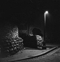 Roger-Viollet | 242805 | World War II. Entrance of a building protected by sand bags. Paris, Winter 1939-1940. | © Gaston Paris / Roger-Viollet