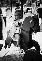 Roger-Viollet | 258158 | Little girl on a carousel on the Champs-Elysées. Paris, 1950's. | © Jacques Rouchon / Roger-Viollet