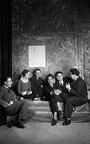 Roger-Viollet | 258811 | Les Six, group of French composers. From left to right : Francis Poulenc, Germaine Tailleferre, Louis Durey, Georges Auric (on the drawing by Jean Cocteau), Jean Cocteau, French writer (who joined the group of composers), Darius Milhaud and Arthur Honegger. 1931. | © Boris Lipnitzki / Roger-Viollet
