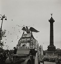 Roger-Viollet | 264984 | Parade at the place de la Bastille. Truck of the left-party magazines. Paris, 1950. Photograph by Janine Niepce (1921-2007). | © Janine Niepce / Roger-Viollet