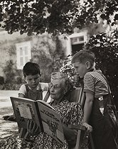 Roger-Viollet | 269535 | Two fans of Tintin with their grandmother. Rully (France), 1952. Photograph by Janine Niepce (1921-2007). | © Janine Niepce / Roger-Viollet