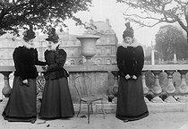 Roger-Viollet | 281171 | Women's fashion. Special effect photograph by Henri Roger.  Bilocation . Paris, Jardin du Luxembourg, about 1895. | © Henri Roger / Roger-Viollet
