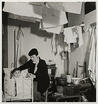 Roger-Viollet | 284055 | Woman with her baby in a room unfit for habitation. Paris (XIth arrondissement), 1937. Photograph by Roger Schall (1904-1995). Paris, musée Carnavalet. | © Roger Schall / Musée Carnavalet / Roger-Viollet