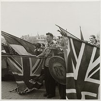 Roger-Viollet | 303763 | Young people carrying French, American and British flags, at a celebration in front of the Arc de Triomphe, place Charles-de-Gaulle-Etoile. Paris (VIIIth, XVIth, XVIIth arrondissements), 1945. Photograph by Roger Schall (1904-1995). Paris, musée Carnavalet. | © Roger Schall / Musée Carnavalet / Roger-Viollet