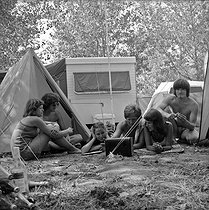 Roger-Viollet | 308133 | Young people listening to the radio with a transistor in a camping site. | © Roger-Viollet / Roger-Viollet