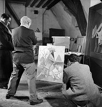 Roger-Viollet   309224   Pablo Picasso (1881-1973), Spanish painter and sculptor, from behind on the left, in his studio, rue des Grands-Augustins. Paris (VIth arrondissement), November 1944.   © Pierre Jahan / Roger-Viollet