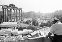 Roger-Viollet | 314136 | Tourist guides seller. In the background, the Forum Romanum. Rome (Italy), 1970's. | © Jean-Pierre Couderc / Roger-Viollet