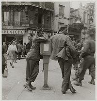 Roger-Viollet | 327182 | World War II. US soldiers leaning on a post box, boulevard Rochechouart. Paris (Xth and XVIIIth arrondissement), 1945. Photograph by Roger Schall (1904-1995). Paris, musée Carnavalet. | © Roger Schall / Musée Carnavalet / Roger-Viollet