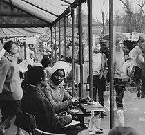 Roger-Viollet | 328228 | Couple at the table of a café terrace. Paris. Photograph by Janine Niepce (1921-2007). | © Janine Niepce / Roger-Viollet