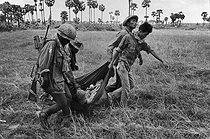 Roger-Viollet | 331769 | Soldiers evacuating another soldier wounded by the Khmer Rouge. Cambodia, 1974. | © Françoise Demulder / Roger-Viollet