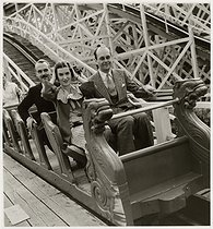 Roger-Viollet | 338447 | Two men and a woman in a seat of the roundabout  Scenic Railway , Luna Park, porte Maillot, Paris (XVIth arrondissement). 1935. Photograph by Roger Schall (1904-1995). Paris, musée Carnavalet. | © Roger Schall / Musée Carnavalet / Roger-Viollet
