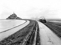 Roger-Viollet | 355107 | View towards the South. The train departure on the dike. Mont-Saint-Michel (France). | © Neurdein / Roger-Viollet