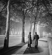Roger-Viollet | 357104 | Avenue de Tokyo by night, two men walking, trees, Paris (XVIth arrondissement). 1938. Photograph by Roger Schall (1904-1995). | © Roger Schall / Roger-Viollet