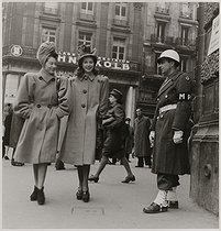 Roger-Viollet | 361818 | Fashion. Women wearing coats, looking at a US soldier. Paris, 1945. Photograph by Roger Schall (1904-1995). Paris, musée Carnavalet. | © Roger Schall / Musée Carnavalet / Roger-Viollet