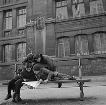 Roger-Viollet | 364206 | Children reading  Le Journal de Mickey , French weekly comics magazine, on a bench. France, 1950's. Photograph by Janine Niepce (1921-2007). | © Janine Niepce / Roger-Viollet