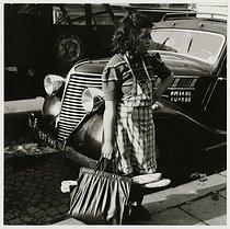 Roger-Viollet | 370281 | Little girl carrying bread, in front of a car, rue Mouffetard, Paris (Vth arrondissement). 1936. Photograph by Roger Schall (1904-1995). Paris, musée Carnavalet. | © Roger Schall / Musée Carnavalet / Roger-Viollet