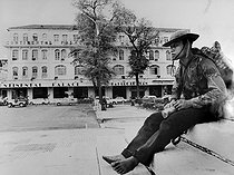 Roger-Viollet | 370738 | Vietnam War (1955-1975). Fall of Saigon. Barefeet Viet Minh soldier eating some bread in front of the Continental Hotel, the luxury hotel of the capital. Saigon (Vietnam), 1975. | © Françoise Demulder / Roger-Viollet