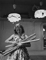 Roger-Viollet | 396457 | Young woman holding baguettes for Saint Catherine's day at Lanvin, rue du Faubourg Saint-Honoré | © Janine Niepce / Roger-Viollet